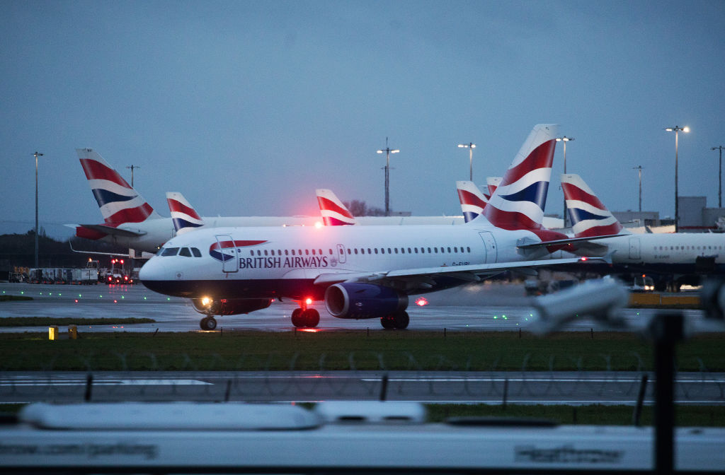 A passenger aircraft operated by British Airways, a unit of International Consolidated Airlines Group SA, on the runway at London Heathrow Airport Ltd. in London, U.K., on Saturday, Dec. 19, 2020. The pandemic has put a third of all tourism jobs at risk, and airlines around the world have said they need as much as $200 billion in bailouts. Photographer: Chris Ratcliffe/Bloomberg via Getty Images